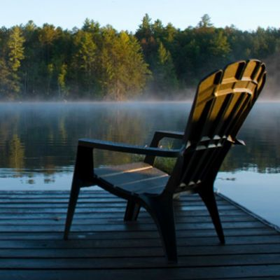 Adirondack chair on deck of misty lake